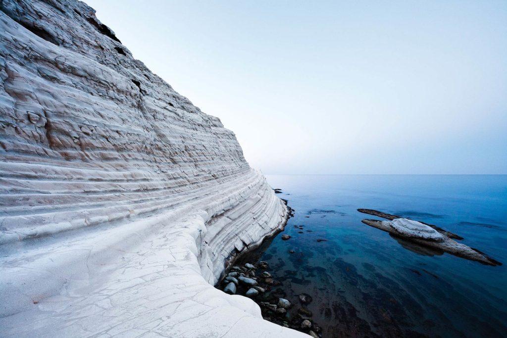 fotografia di paesaggio, mare, terra, scogli bianchi e cielo blu