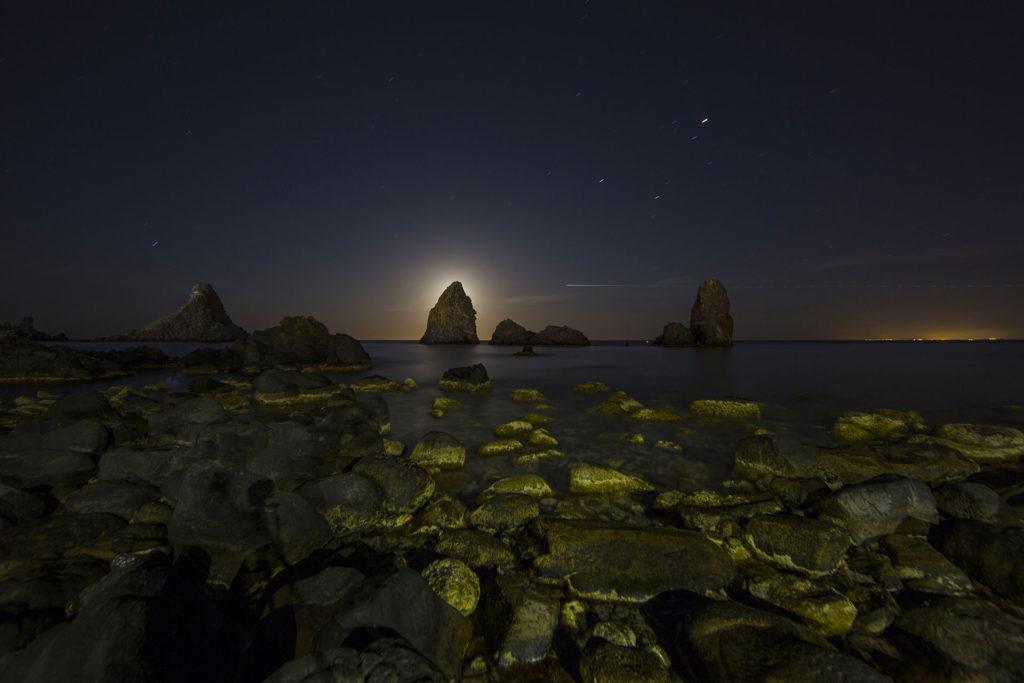 fotografia di paesaggio, mare, notturno, scogli, faraglioni, e luna nascosta