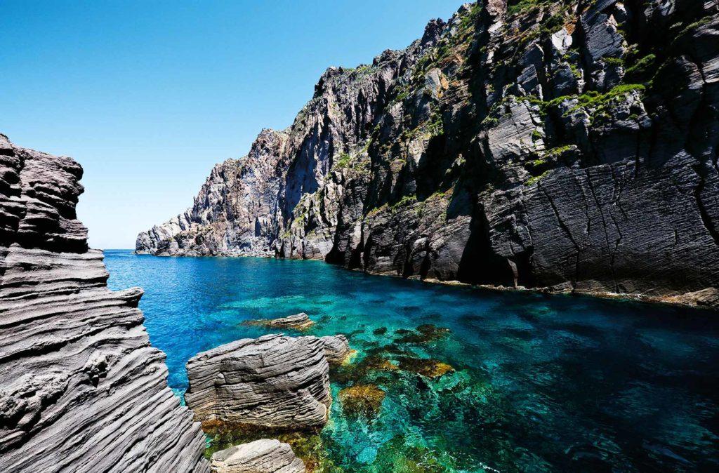 fotografia di paesaggio, mare, terra, scogli e cielo blu